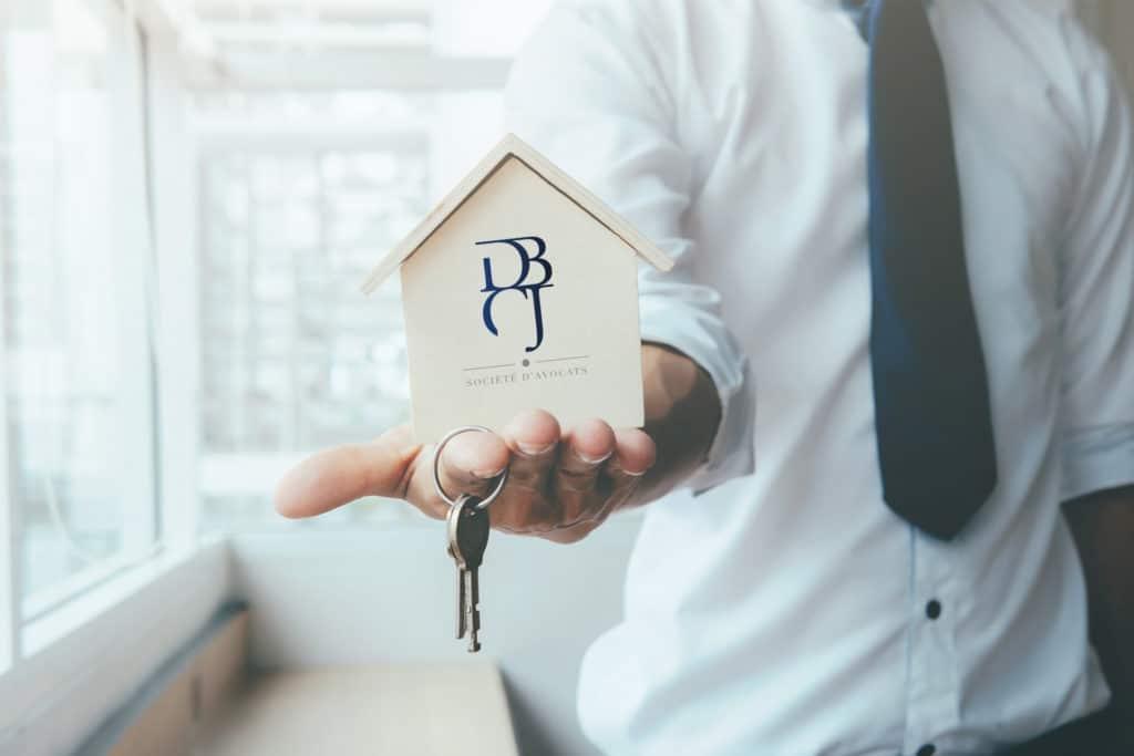 Main tendue portant une petite maison et un jeu de clefs logo DBCJ Avocats