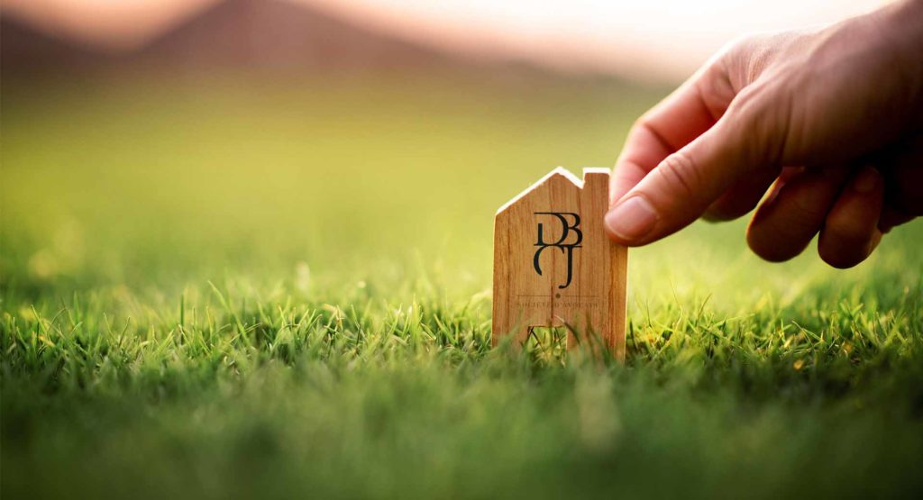 Maison en bois tenue par une main dans l'herbe, Ventes aux enchères terrain